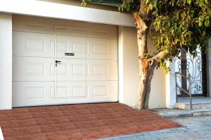 باب كراج لونه أبيض وبه أشكال مستطيلة وداخله باب صغير على يساره شجرة وأمامه منزلف لونه بني